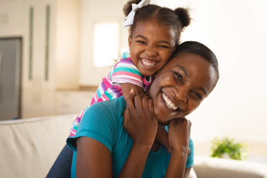 Portrait of happy african american mother and daughter embracing on couch and smiling to camera
