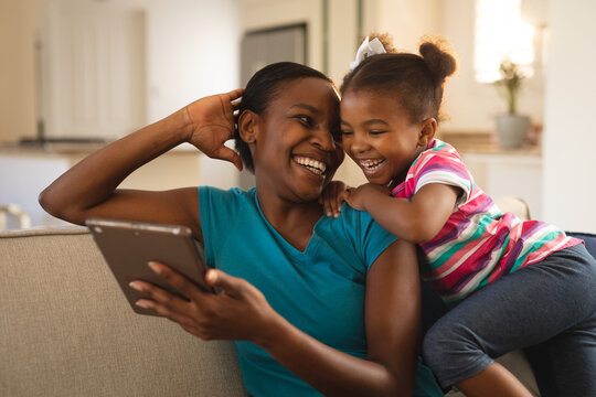 Happy african american mother and daughter relaxing on couch looking at tablet and laughing together