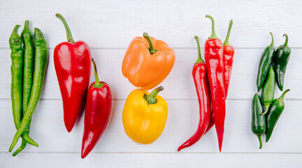top view of various types of peppers bell peppers with green and red hot chili peppers on white background