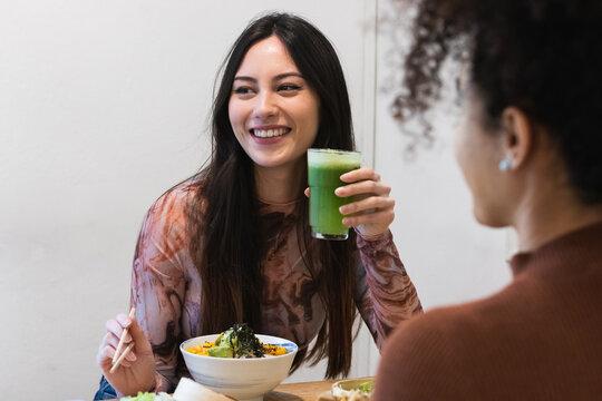 Cheerful diverse women drinking smoothie in restaurant