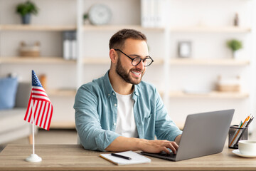 Happy young guy with flag of the US working at desk with laptop in home office