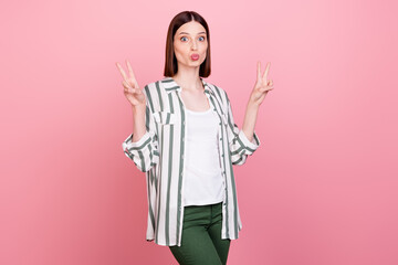 Photo of impressed brunette millennial lady show v-sign blow kiss wear white shirt top isolated on pink color background Wall mural