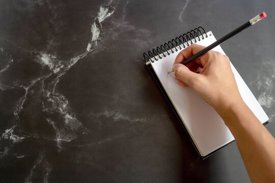 Writing pencil in notepad, on black marble. Selective focus.