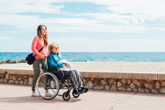 Daughter pushing wheelchair with aged mother on embankment