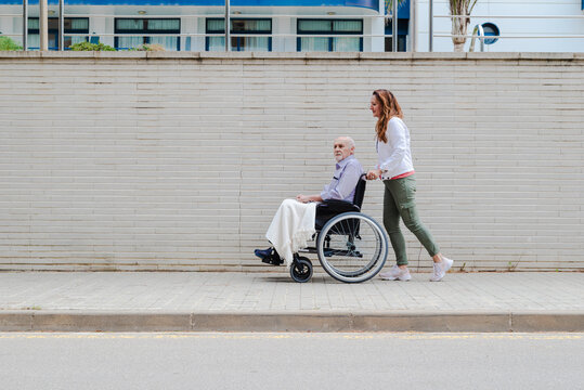 Woman pushing wheelchair with aged man in city street