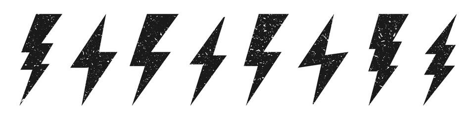 Fototapeta Lightning bolt icons with grunge texture isolated on white background. Vintage flash symbol, thunderbolt. Simple lightning strike sign. Vector illustration. obraz