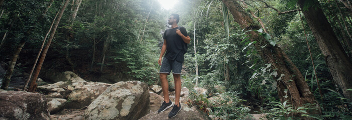 Obraz Male tourist on the stones in the rainforest. - fototapety do salonu