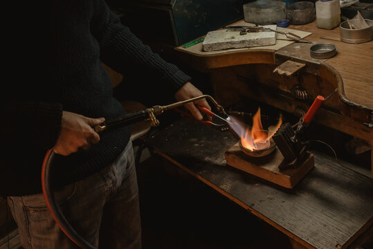 Crop jeweler melting metal with torch
