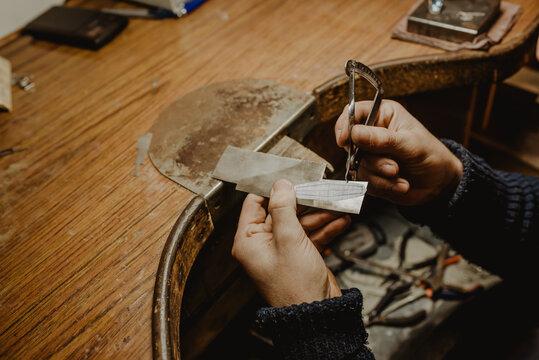 Crop hands measuring metal with caliper