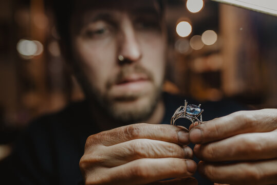 Goldsmith inspecting ring at workshop