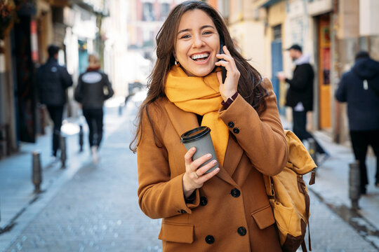 Happy woman with takeaway coffee speaking on smartphone in town