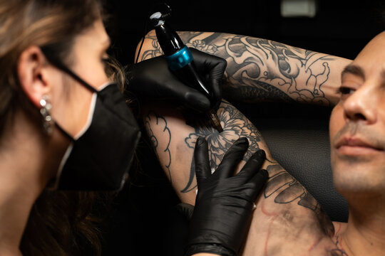 Woman in mask making tattoo for man in salon