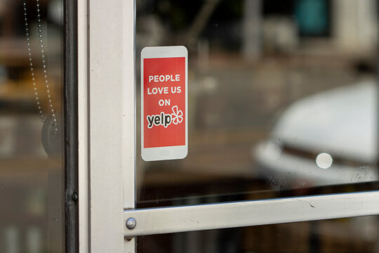 Milwaukie, OR, USA - Jun 18, 2021: Yelp sticker is seen at the entrance to a restaurant in downtown Milwaukie, Oregon. Yelp operates an online platform that connects people with local businesses.