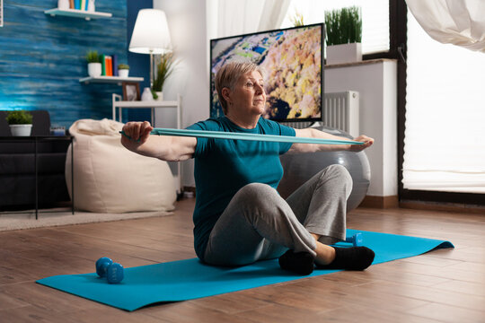 Retired senior woman sitting on yoga mat in lotus position stretching arms muscles using stretch elastic band during wellness sport routine in living room. Pensioner exercising body resistance