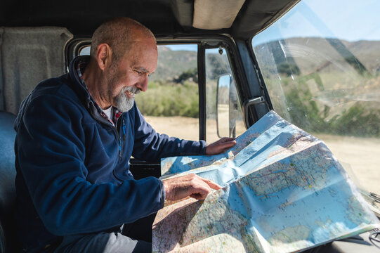 Concentrated travelling man reading map in car