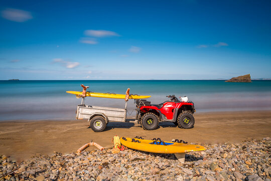 Life guard red quad bike and yellow surf board on the beach