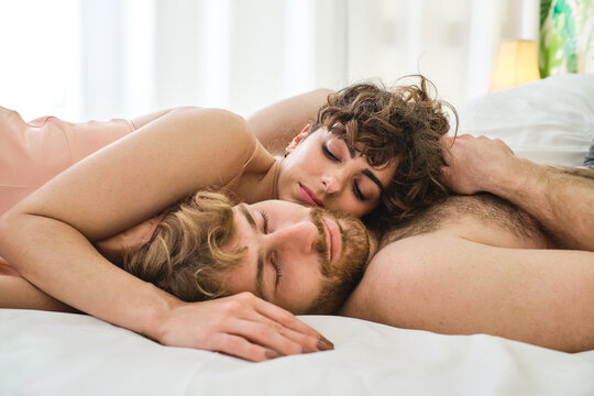 Couple lying on bed and hugging in morning in nightwear