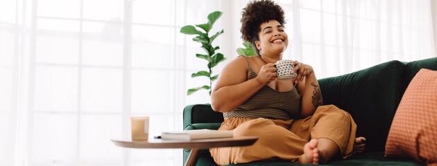 Obraz Smiling woman sitting on sofa having coffee - fototapety do salonu