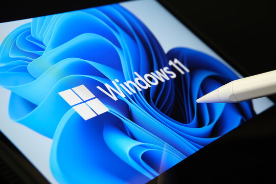 Windows 11 logo seen on the screen of tablet and user pointing at it with stylus. Stafford, United Kingdom, July 1, 2021