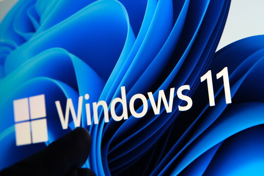Windows 11 logo seen on the screen of tablet and user pointing at it with finger. Stafford, United Kingdom, July 1, 2021