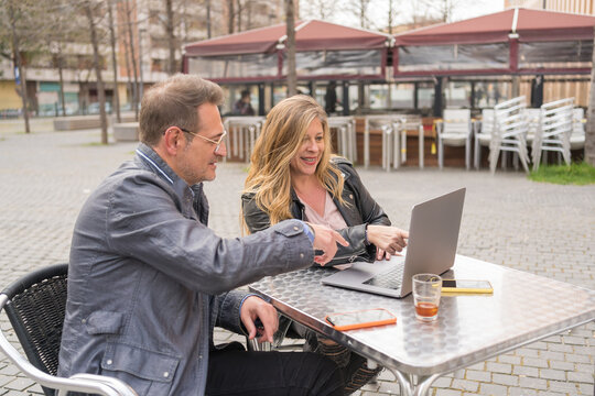 Cheerful middle aged couple using laptop in street cafe