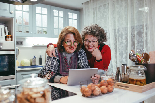Lesbian couple having video call on tablet in kitchen