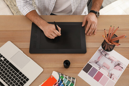 Professional designer with graphic tablet at wooden table, closeup