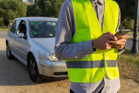 Man in safety vest using smartphone near broken car