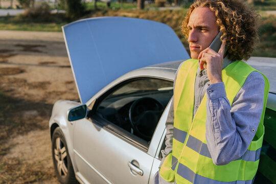 Man calling to repair service near broken car