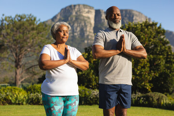 Senior african american couple meditating and practicing yoga with eyes closed in countryside