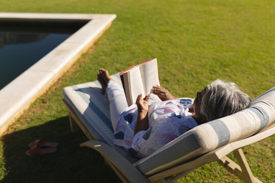 Senior african american woman reading book in deckchair by swimming pool in sunny garden