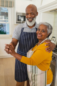 Portrait of senior african american couple in kitchen looking at camera and smiling