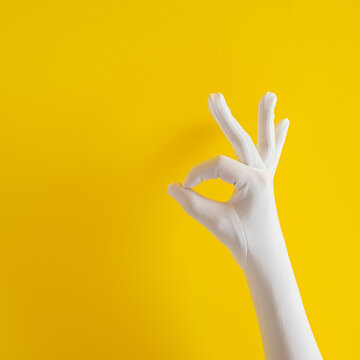 hands with white glove on yellow sunny summer background. modern summer abstract art. mimalism