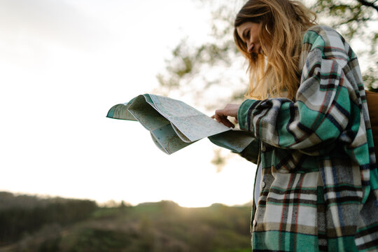 Hiker with paper map in countryside field