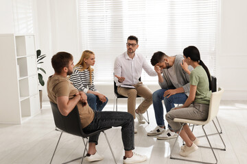 Obraz Psychotherapist working with group of drug addicted people at therapy session indoors - fototapety do salonu