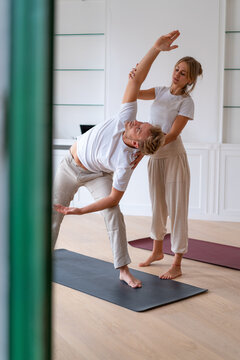 Man doing yoga with instructor in studio