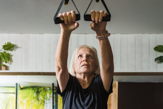 Senior sportswoman exercising with straps on light background
