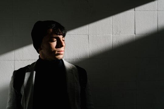 Stylish man standing near wall lit by sunlight