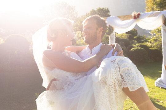 Happy caucasian bride and groom getting married, groom carrying bride