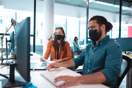 Two diverse businesspeople wearing face mask using computer