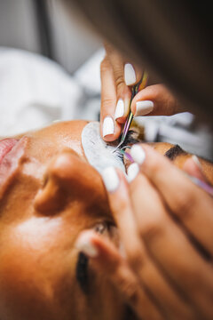 Crop beautician applying eyelashes on face of black woman