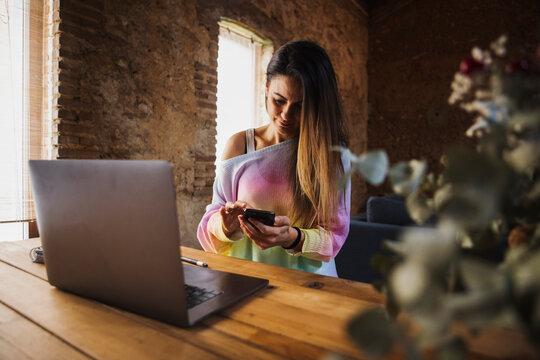 Freelancer chatting on smartphone at table with laptop at home