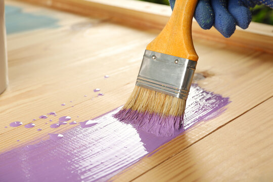 Worker applying violet paint onto wooden surface, closeup