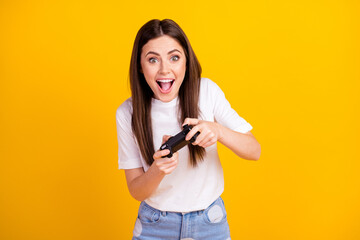 Photo of young excited girl happy positive smile play video game console isolated over yellow color background Wall mural