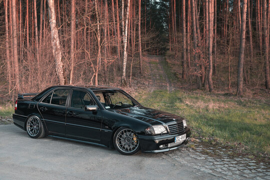 Goleniow, Poland - April 20th, 2021: Old black tuned Mercedes Benz C-class (W202 model) near forest. Compact luxury sedan icon from the 90s. Side view