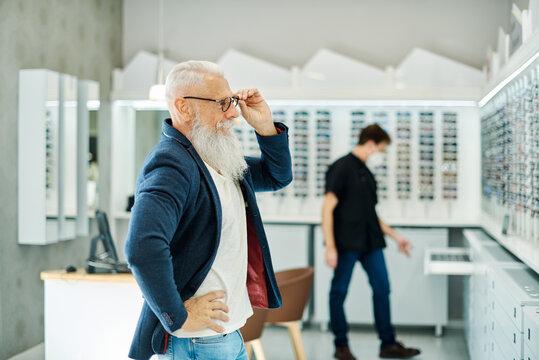Optician helping aged man choosing glasses in optical shop