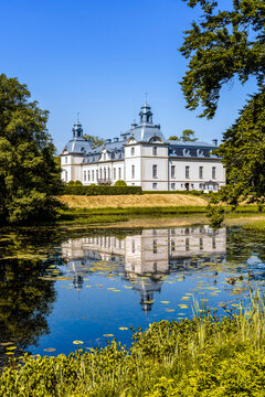 picturesque Kronovall Castle and gardens reflected in a pond in the foreground on a summer dday under a blue sky