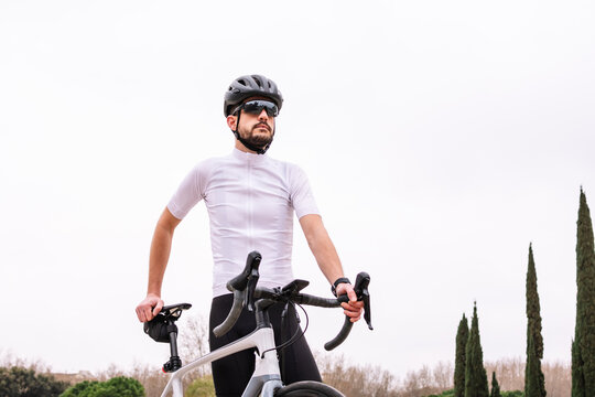 Bearded biker in sunglasses with bicycle under white sky