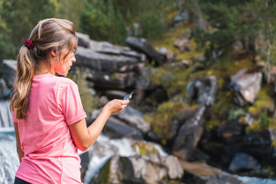 Traveling woman using compass in mountains
