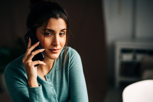 Smiling woman speaking on smartphone in house